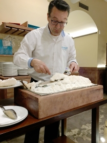 waiter removing a salt crust from a fish that has been cooked in it