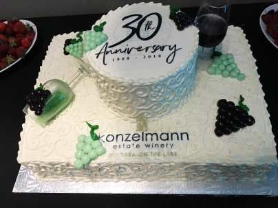 "Konzelmann 30th Anniversary cake, quite ornate with icing shaped like grape clusters and two glasses of decorative ""wine"""
