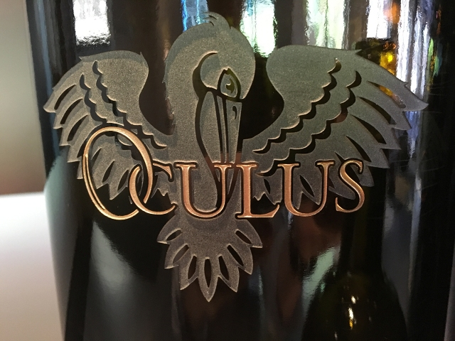 Oculus bottle close up, showing name and pelican logo etched into glass